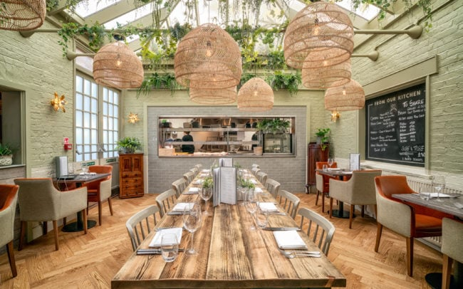 Contemporary restaurant design - large group table with kitchen view
