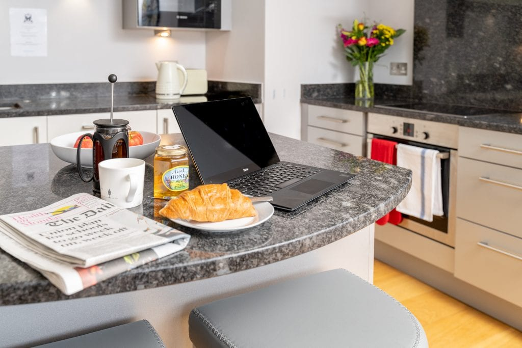 Serviced Apartment kitchen island showing laptop set up for business breakfast