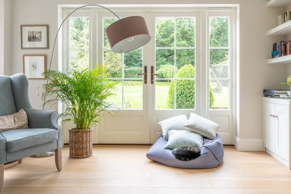 Light and airy living space showing a cat sleeping on a cushion, high quality seating and views into the garden